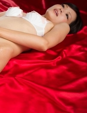 White lingerie hottie Ryo Yuuki masturbates furiously on a big red bed right here